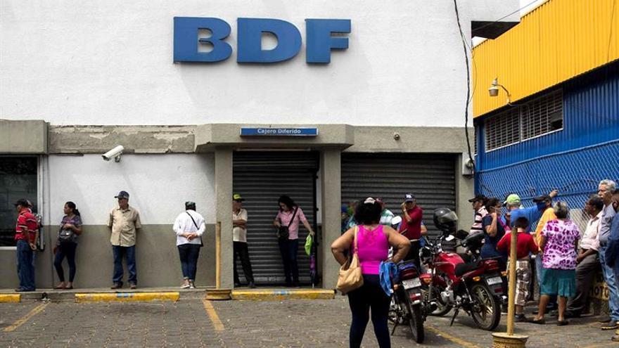 Varios adultos mayores hacen fila para retirar su pensión de jubilación en un banco este martes, en Managua (Nicaragua).