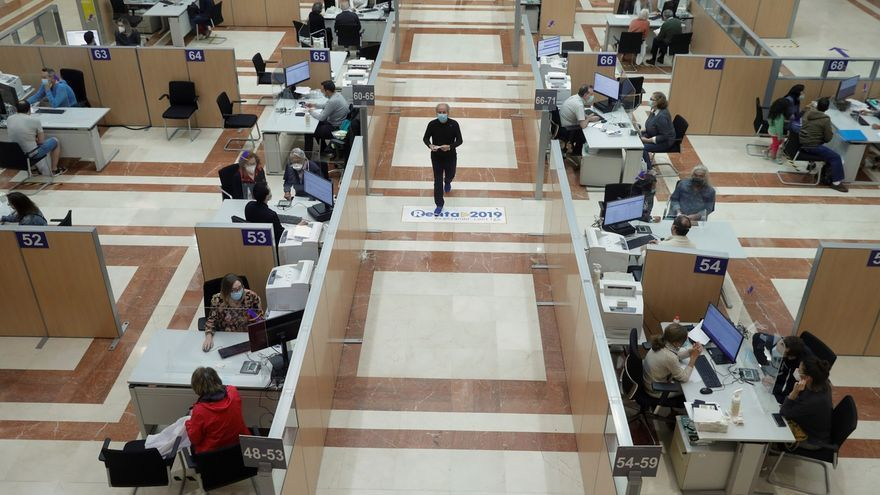 Varias personas son atendidas presencialmente para elaborar el borrador de la renta de 2019 en la sede de la delegación de Hacienda de Guzmán el Bueno en Madrid.