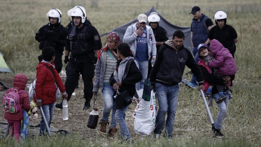 Una familia de refugiados lleva sus pertenencias durante la operación policial en el campo de refugiados improvisado en la frontera entre Grecia y Macedonia, cerca del pueblo griego de Idomeni. | Yannis Kolesidis / ANA-MPA a través de AP