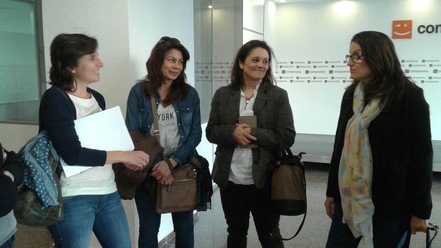 Tres representantes de la asociación de víctimas del metro con Mónica Oltra (a la derecha) en la sede de Compromís.