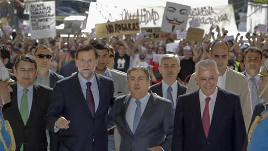 Juan Ignacio Zoido entrando entre protestas en el Ayuntamiento de Sevilla junto a Mariano Rajoy y Javier Arenas, en 2011