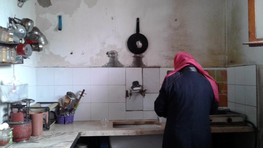 Una mujer lava los platos en su casa / Amjda Shabat