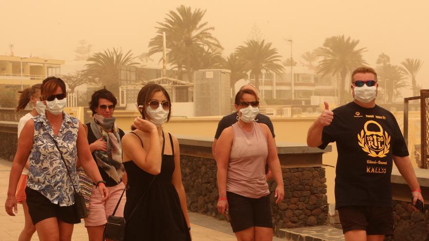 Turistas pasean al sur de Gran Canaria en un día de intensa calima.