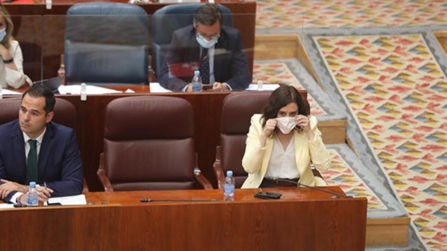 La presidenta de la Comunidad de Madrid, Isabel Díaz Ayuso (d), se pone la mascarilla durante una sesión plenaria en la Asamblea de Madrid.