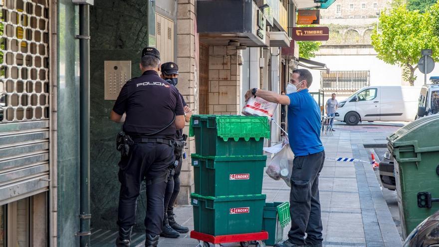 Miembros de la Policía Nacional hablan con un repartidor mientras montan guardia frente al edificio en la calle Nicolás Salmerón de Santander, en aislamiento por coronavirus.