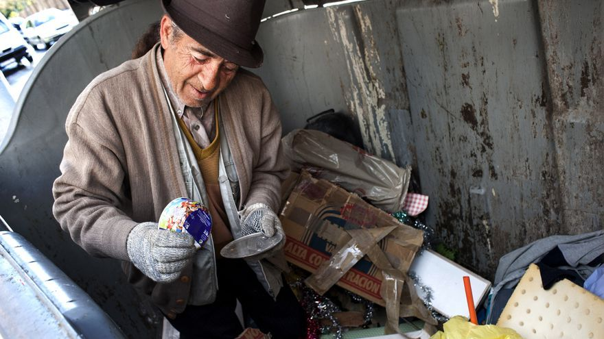 Un anciano recoge comida de un contenedor de basura