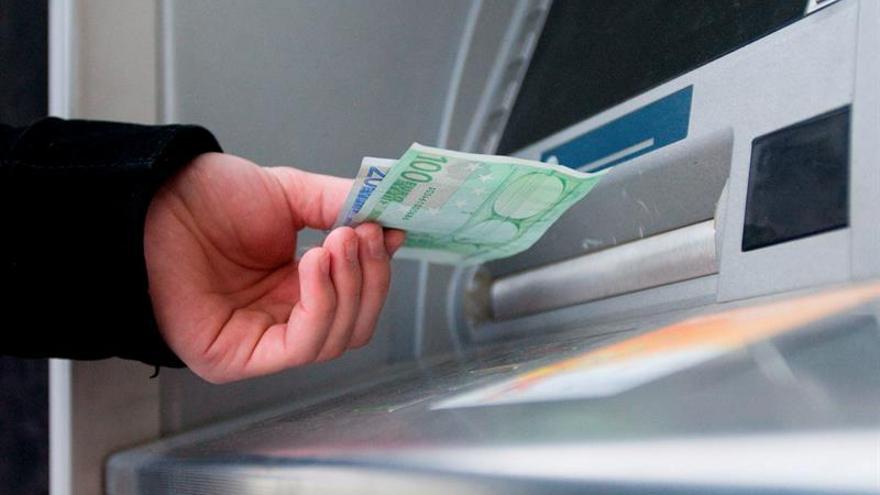 Un consumidor saca dinero de un cajero automático.