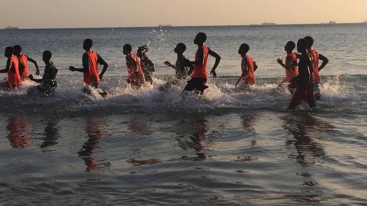 Jóvenes de la African Football Academy entrenando en la playa