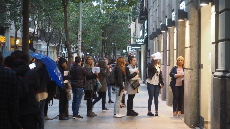 Un grupo de aspirantes hace cola bajo la lluvia  en la puerta de la tienda para hacer la entrevista de trabajo.