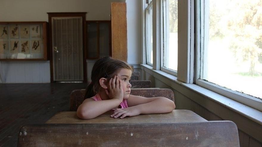 Una niña mira distraída por la ventana