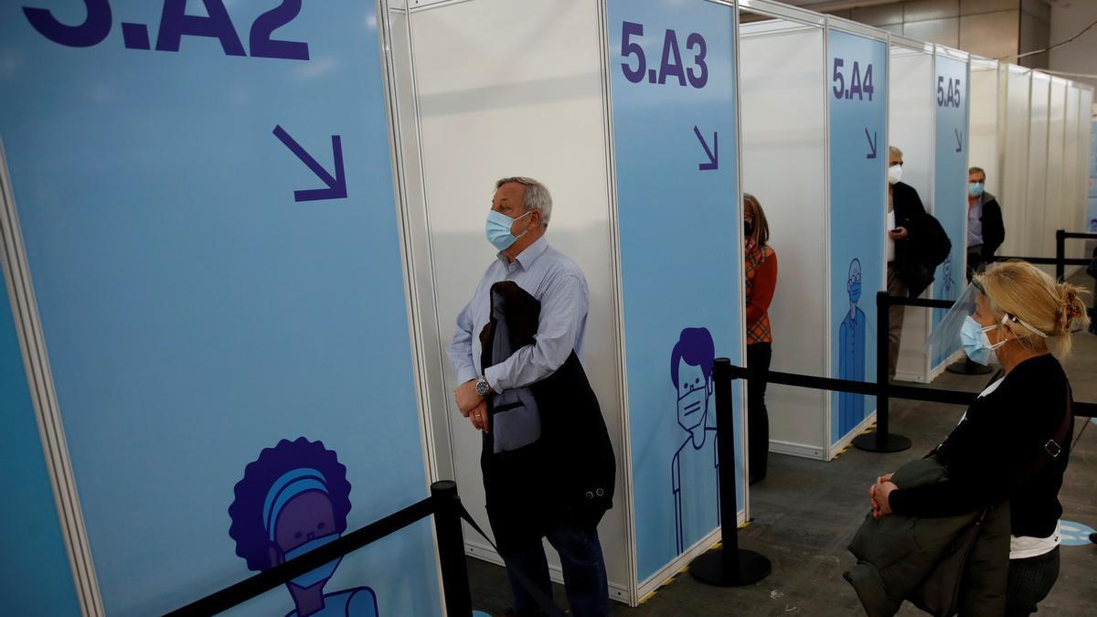 Un grupo de personas esperan a ser vacunados contra la COVID 19 en el pabellón número cuatro de la Fira de Barcelona, que ha acogido este lunes la primera prueba piloto de vacunación.
