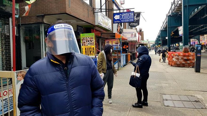 People with facial masks walk at a street in Queens, New York, 17 April 2020.
