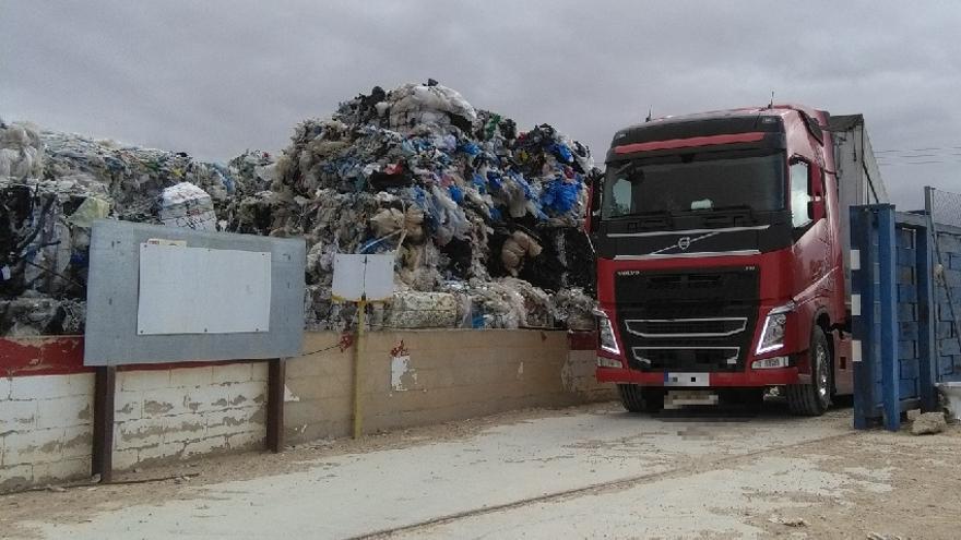 Un camión trabaja en la retirada de los residuos plásticos de la planta Utiel Recicla