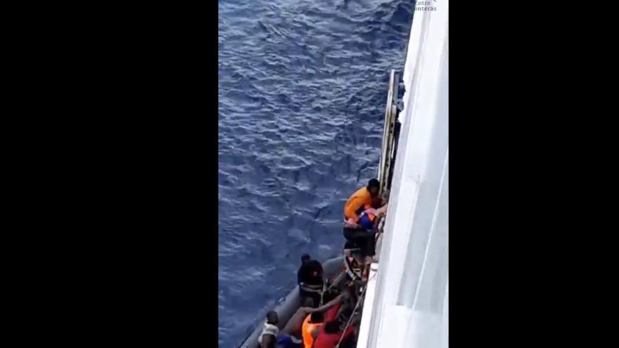 Los supervivientes de la patera naufragada suben al ferry que los ha localizado a través de una cuerda.