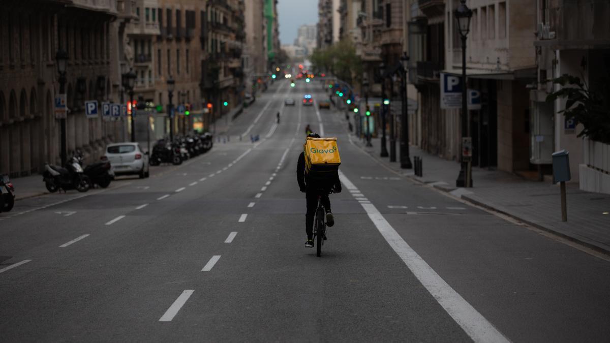 Un trabajador de Glovo en bicicleta por Via Laietana durante los días de confinamiento