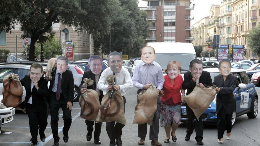 Activists of World Vision, a Christian relief, development and advocacy organization, wearing masks of the G8 (Group of Eight) leaders, from left, Russian President Dmitry Medvedev, Canadian Prime Minister Stephen Harper, British Prime Minister Gordon Brown, US President Barack Obama, Italian Premier Silvio Berlusconi, German Chancellor Angela Merkel, French President Nicolas Sarkozy and Japanese Prime Minister Taro Aso, simulate a robbery, during a protest in Rome, Monday, July 6, 2009, ahead of the upcoming G8 summit in L'Aquila, from July 8 to July 10.