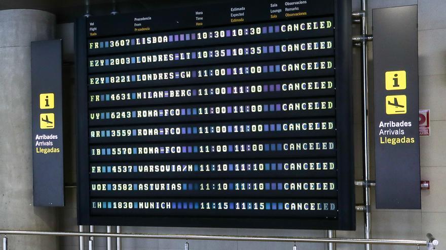 Archivo - Pantalla luminosa en la que se muestran varios vuelos cancelados