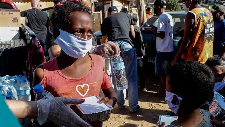 Fotografía fechada el 31 de mayo de 2020 de niños recibiendo una donación de alimentos en la comunidad de Capadócia, en Brasilandia, un barrio en la periferia de la ciudad de São Paulo (Brasil).