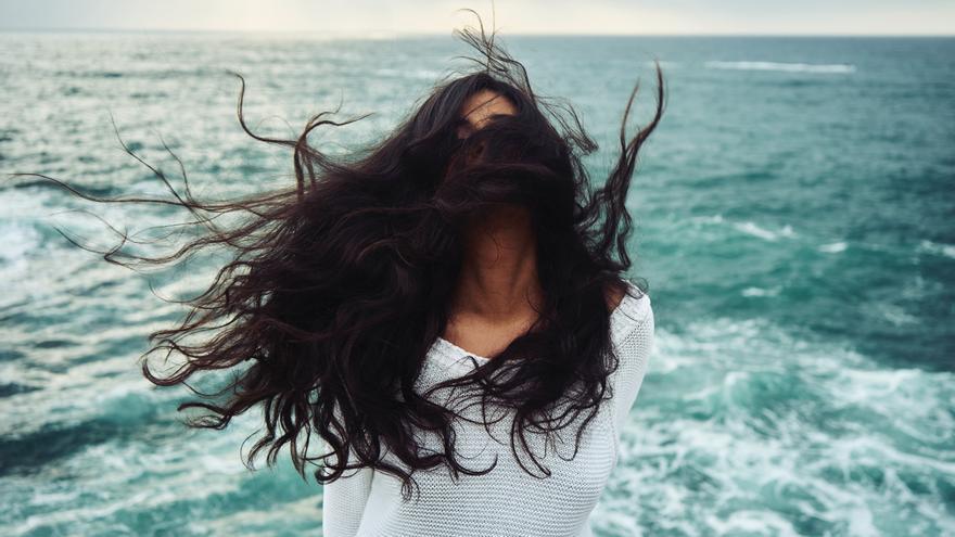 Mujer con pelo al viento en la playa