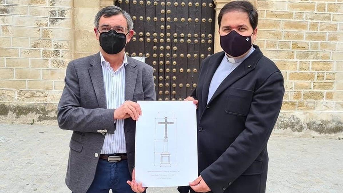 El presidente de la Agrupación de Cofradías de Aguilar, José Cabezas, presenta el boceto de la nueva cruz junto al párroco de Aguilar Pablo Lora.