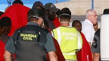 Miembros de la Guardia Civil ayudan a los 68 inmigrantes rescatados por Salvamento Marítimo a su llegada al muelle de Gran Tarajal (Fuerteventura), este lunes.