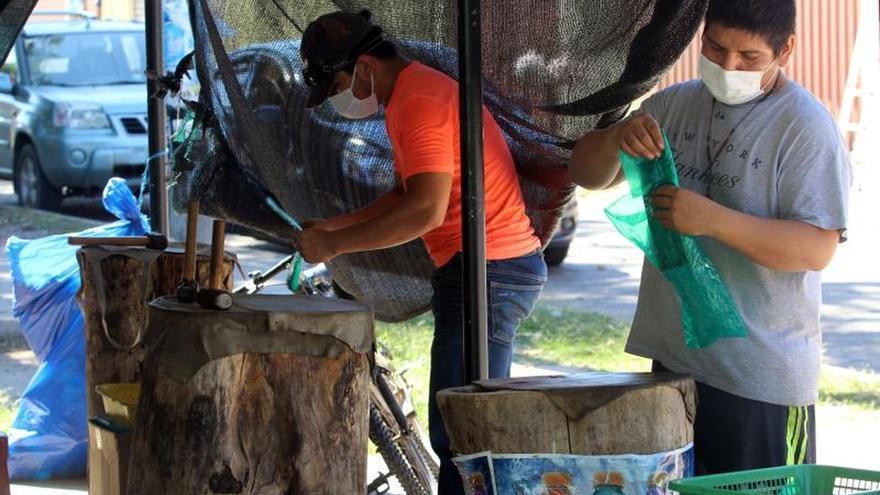 """Dos hombres con tapabocas preparan el viernes 29 de mayo hoja de coca """"machucada"""", en Santa Cruz (Bolivia). El negocio cayó como muchos otros al tener que quedarse la gente en casa por la pandemia del coronavirus, pero la venta de hoja de coca """"machucada"""", como se conoce en Bolivia, también espera recuperarse poco a poco."""
