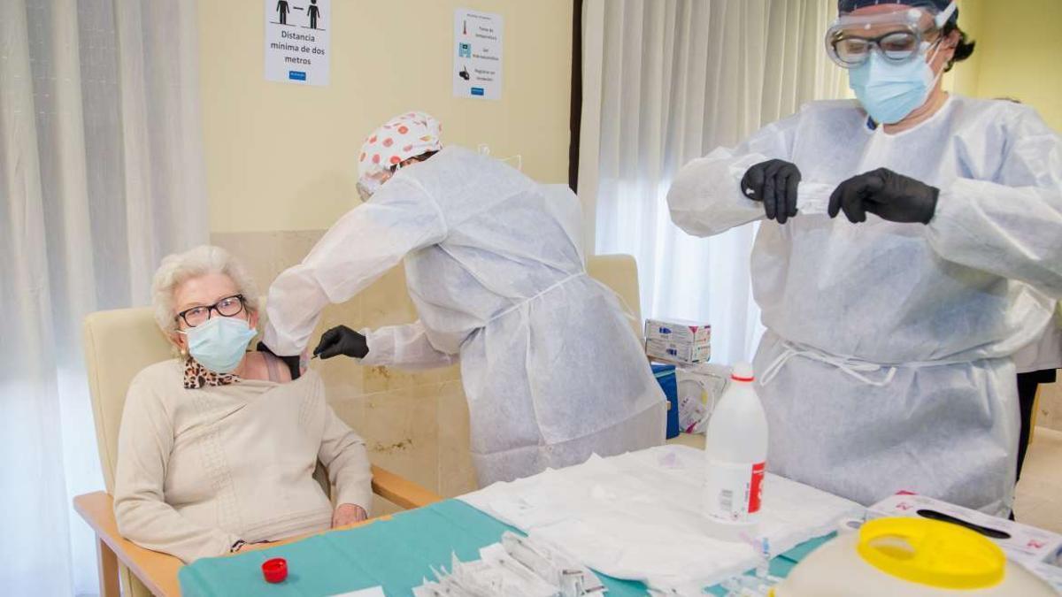 Dos enfermeras vacunan a una anciana contra el coronavirus.