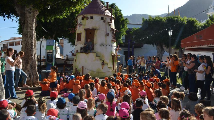Alumnos ubicados en la plaza central del pueblo atienden a la historia que cuenta un narrador