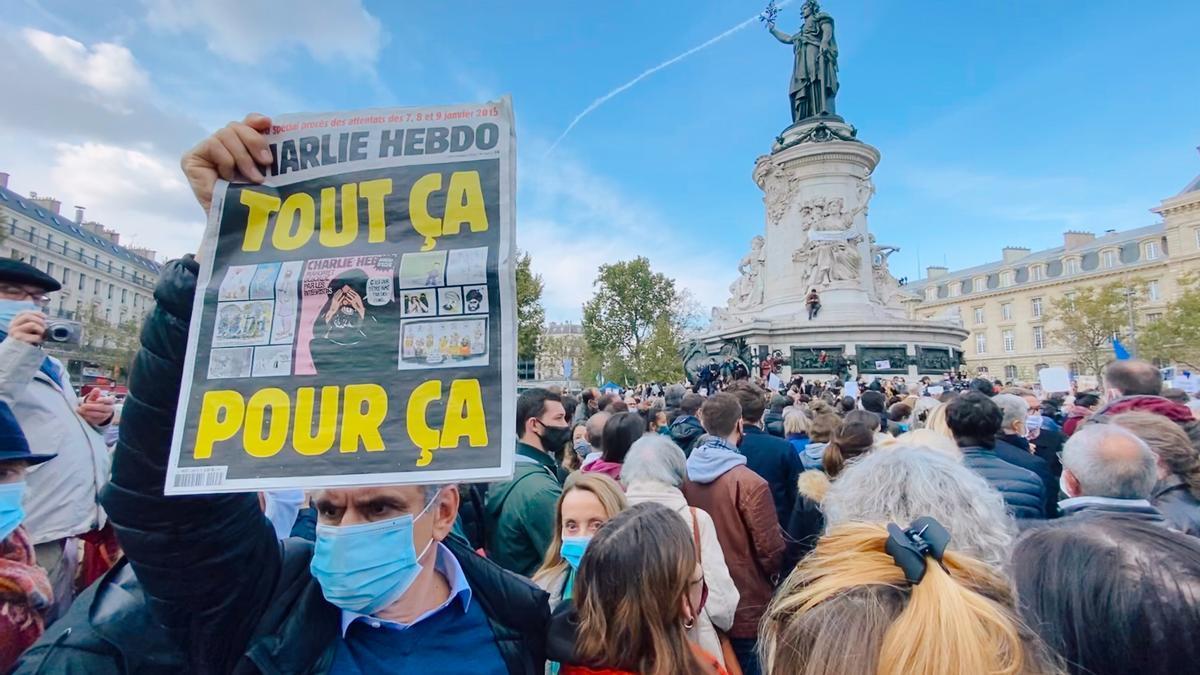 Uno de los asistentes a la manifestación muestra una portada de Charlie Hebdo.