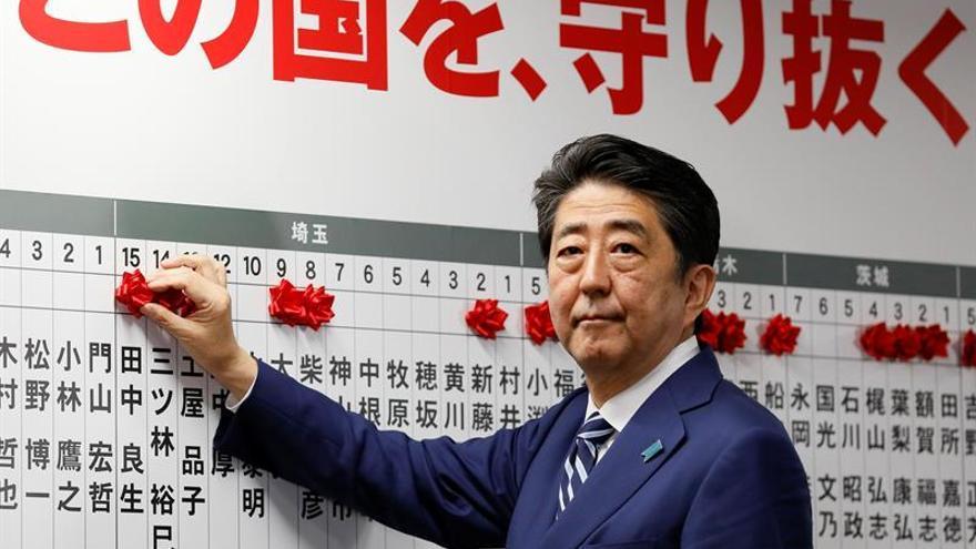 El primer ministro japonés, Shinzo Abe, pone una rosa roja en el nombre del candidato para ser elegido en los comiscios de la Cámara Baja, en la sede del gobernante Partido Liberal Democrático (PDL) en Tokio, Japón.