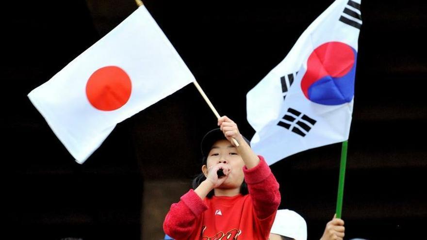 Dos jóvenes ondean banderas de Japón y de Corea del Sur.