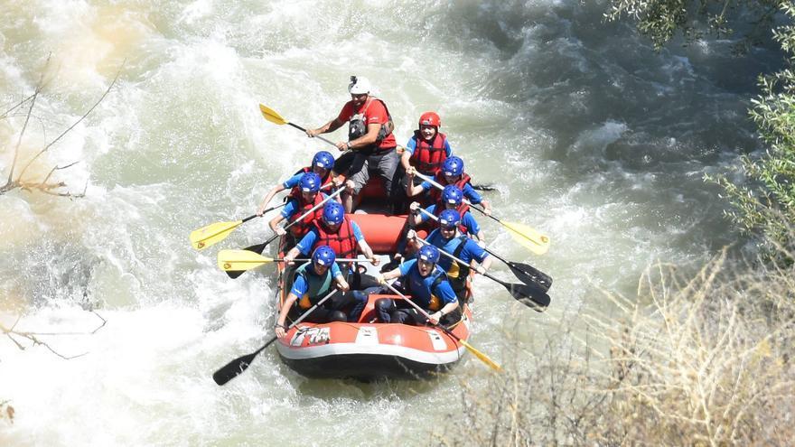 Un grupo de personas practicando rafting en el río Genil.