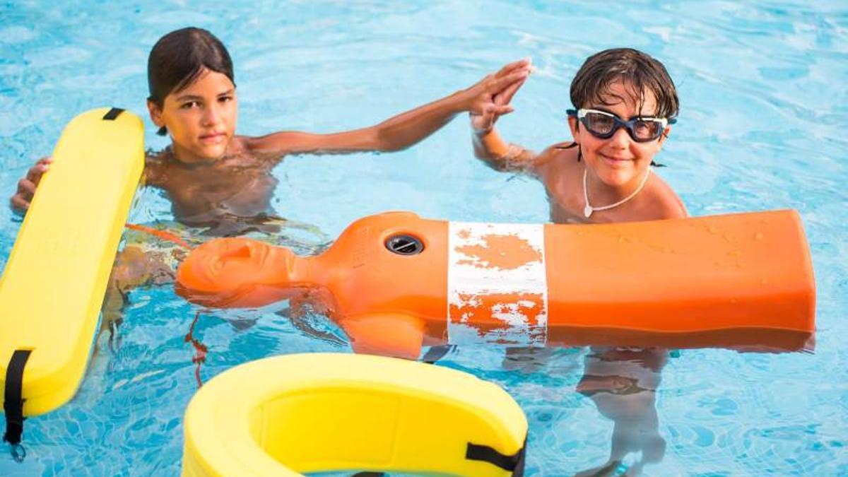 Dos niños se felicitan tras haber realizado una práctica con un maniquí y sendos tubos de rescate