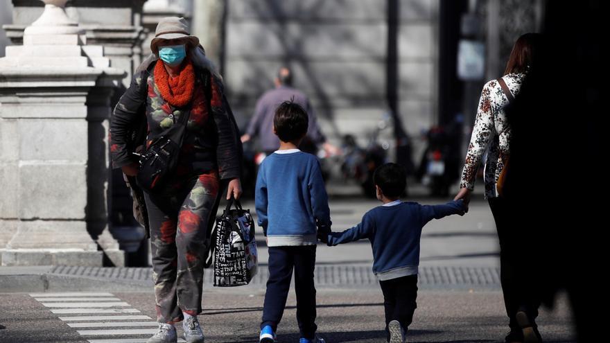 Una mujer con mascarilla se cruza con una familia en un paso de cebra de Madrid.
