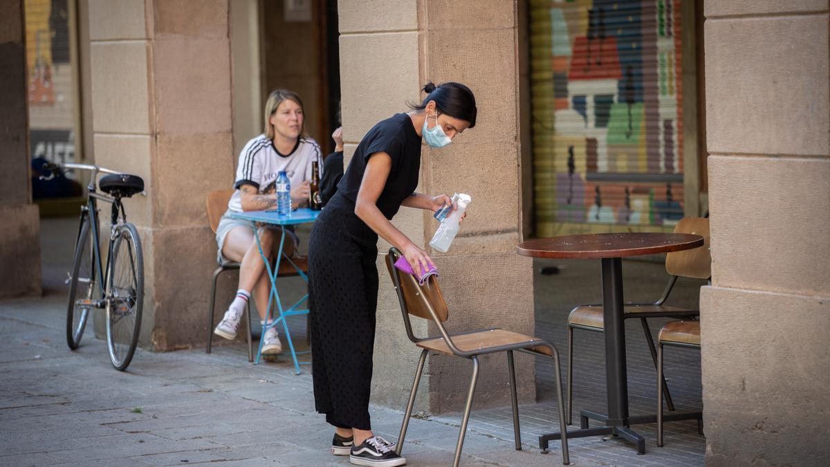 Una camarera limpia varias sillas y una mesa de la terraza de un bar
