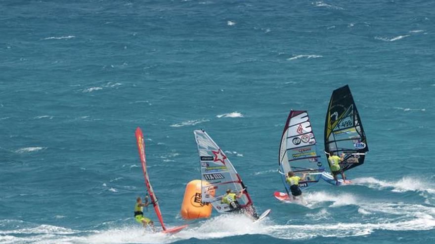 Varios turistas observan la prueba de slalom del Campeonato del Mundo de Windsurfing y Kiteboarding de Fuerteventura