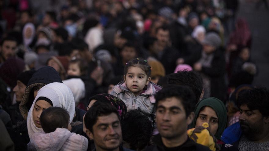 Una familia con su hija a hombros aguarda la llegada del ansiado ferry que los llevará a Atenas / Foto: Olmo Calvo