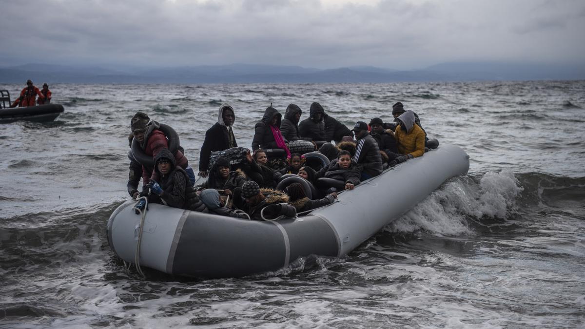 Migrantes de África sentados en un bote de goma al llegar de Turquía a la playa de la aldea de Skala Sikamineas (Grecia) el pasado febrero.