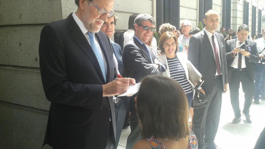 Rajoy firma un autógrafo a una niña tras la sesión constitutiva de las Cortes.
