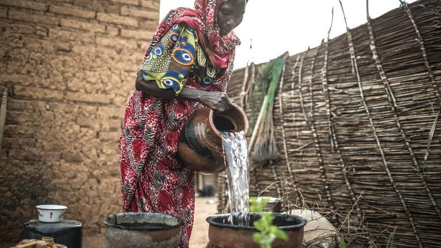 Akkoe Moussa, echando agua potable en un cántaro de cerámica / FOTO: Pablo Tosco - Oxfam Intermón