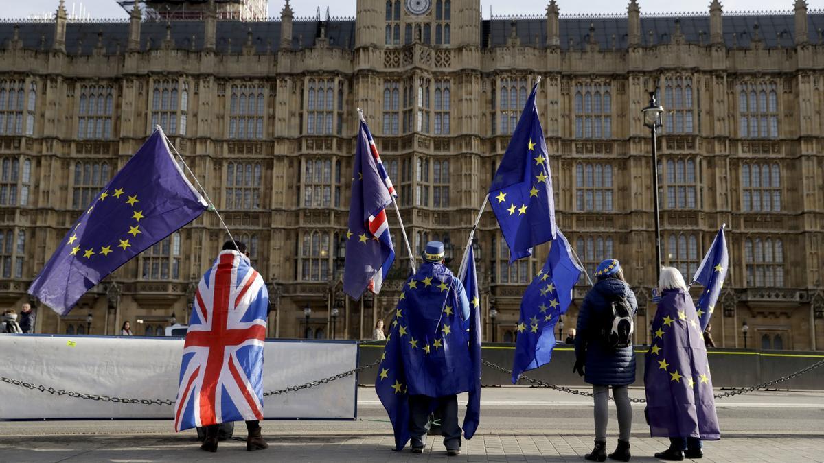Partidarios de la UE sostienen banderas de la Unión Europea mientras protestan contra el Brexit frente al Parlamento en Londres.