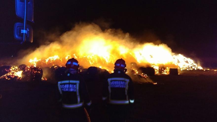 Bomberos del 112 trabajan en la extinción de un incendio en una pila de 1.500 pacas en Requejo