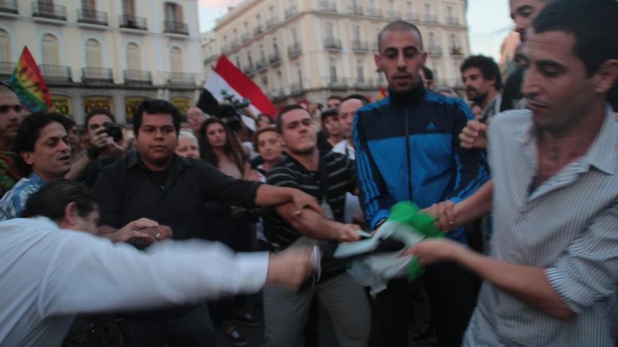 Varios asistentes a la manifestación intentaron arrancarle la bandera de la oposición siria. / Isabel Montenegro