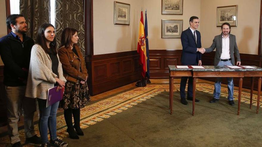 Pedro Sánchez y Pablo Iglesias se dan la mano tras firmar el acuerdo, observados por Adriana Lastra, Irene Montero y Alberto Garzón.