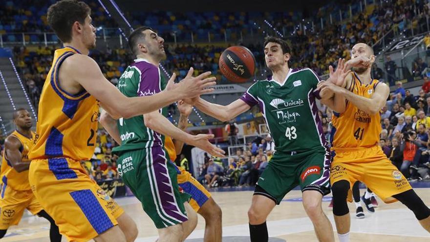 El base estadounidense del Herbalife Gran Canaria, Clevin Hannah (c), con el balón ante el jugador serbio de Unicaja, Dragan Milosavvljevic, durante el encuentro de la liga ACB disputado este sábado en el Gran Canaria Arena, en Las Palmas de Gran Canaria.