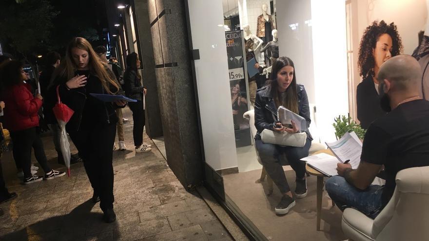 Una candidata hace la entrevista de trabajo en el escaparate mientras el resto de las aspirantes espera en la calle.