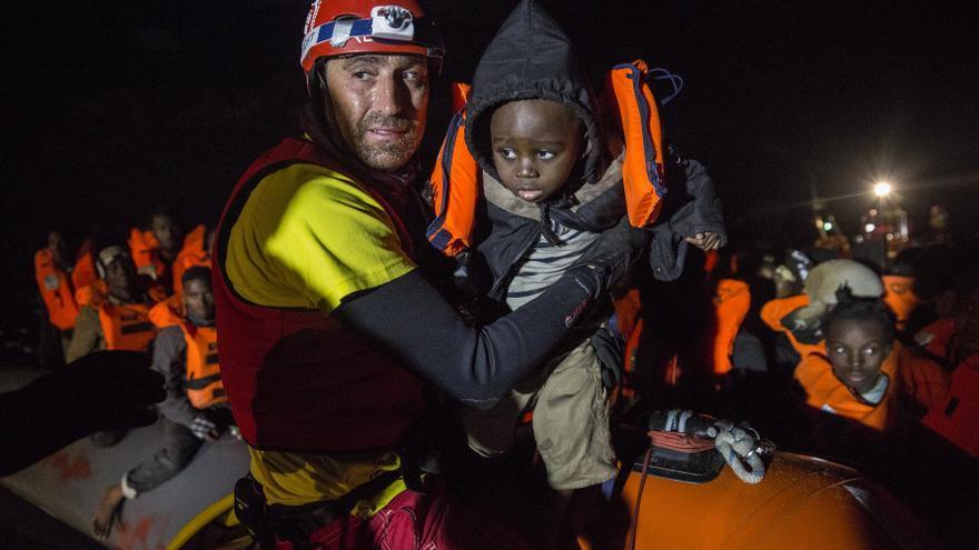 Un miembro de Proactiva Open Arms saca de la barcaza a uno de los niños