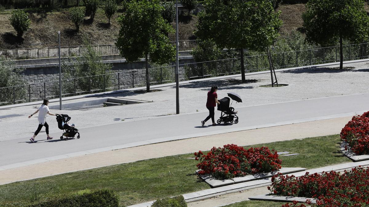 Dos madres con carritos de bebé pasean en Madrid Río.