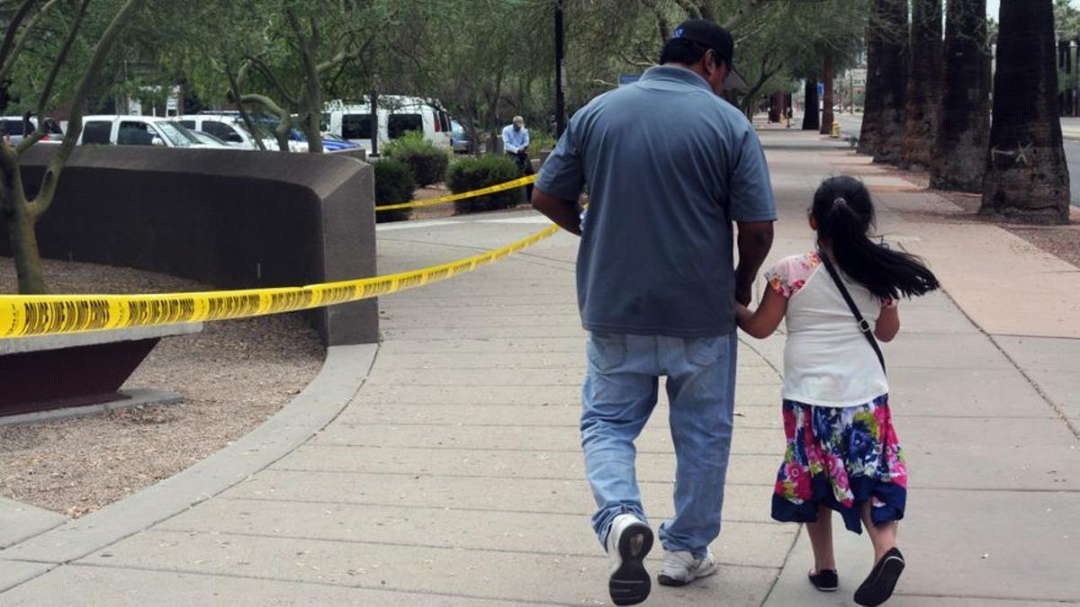 Un hombre camina junto a su hija tras salir de una cita en la Oficina de Control de Inmigración y Aduanas en Phoenix, Arizona.