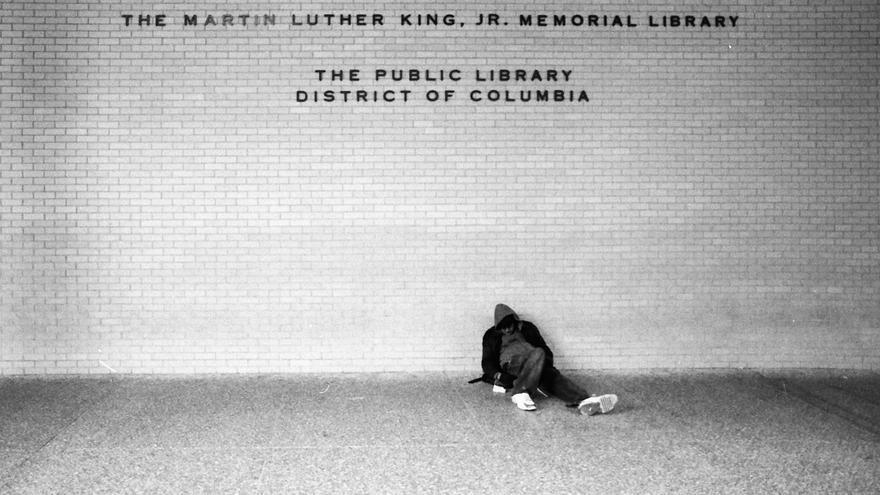 Una persona sin techo duerme afuera de la biblioteca pública dedicada a Martin Luther King Jr..